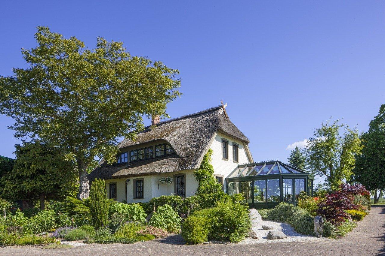 Grande maison entourée d'arbre avec une véranda