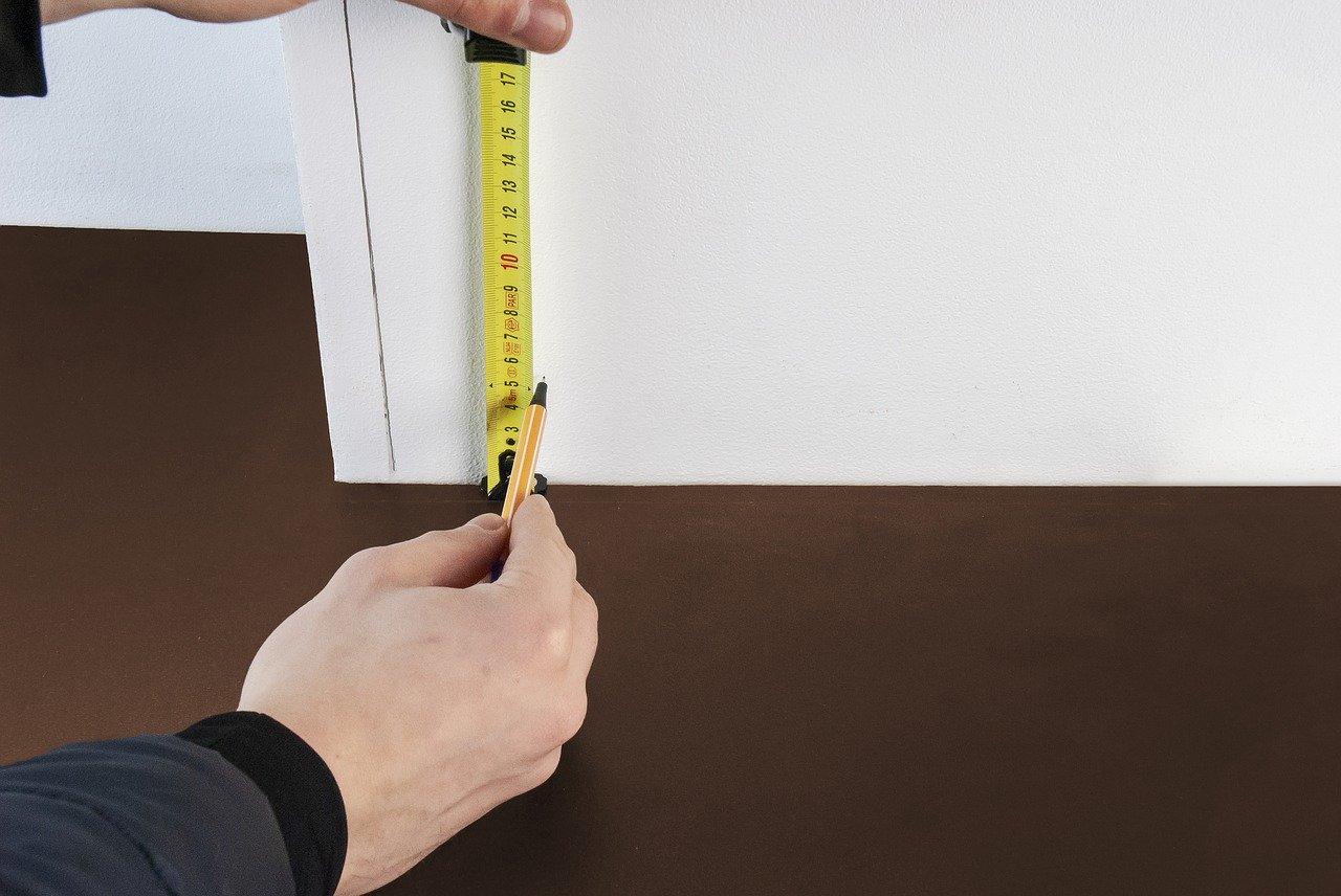 Personne prenant des mesure pour installer plinthes