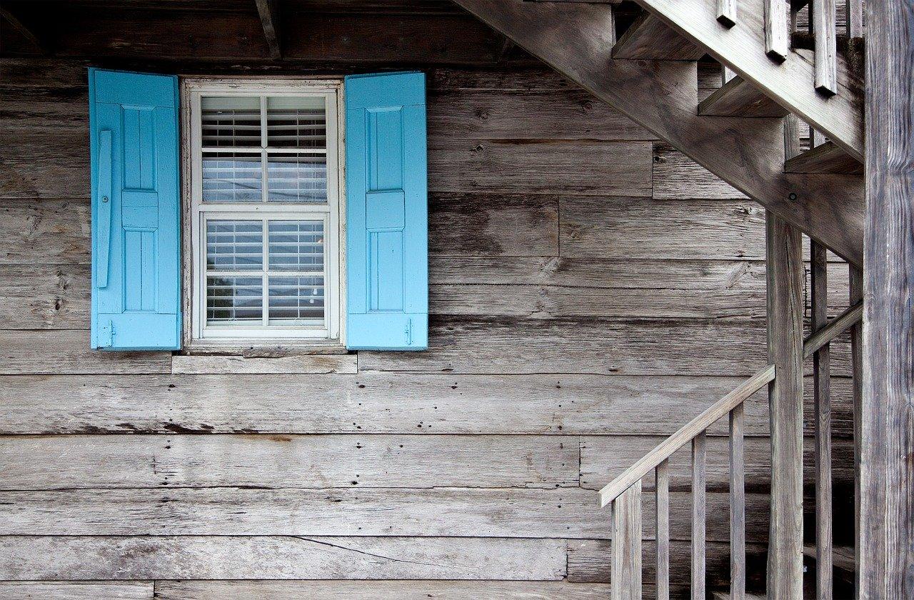 Volet bleu sur une maison en bois en noir et blanc