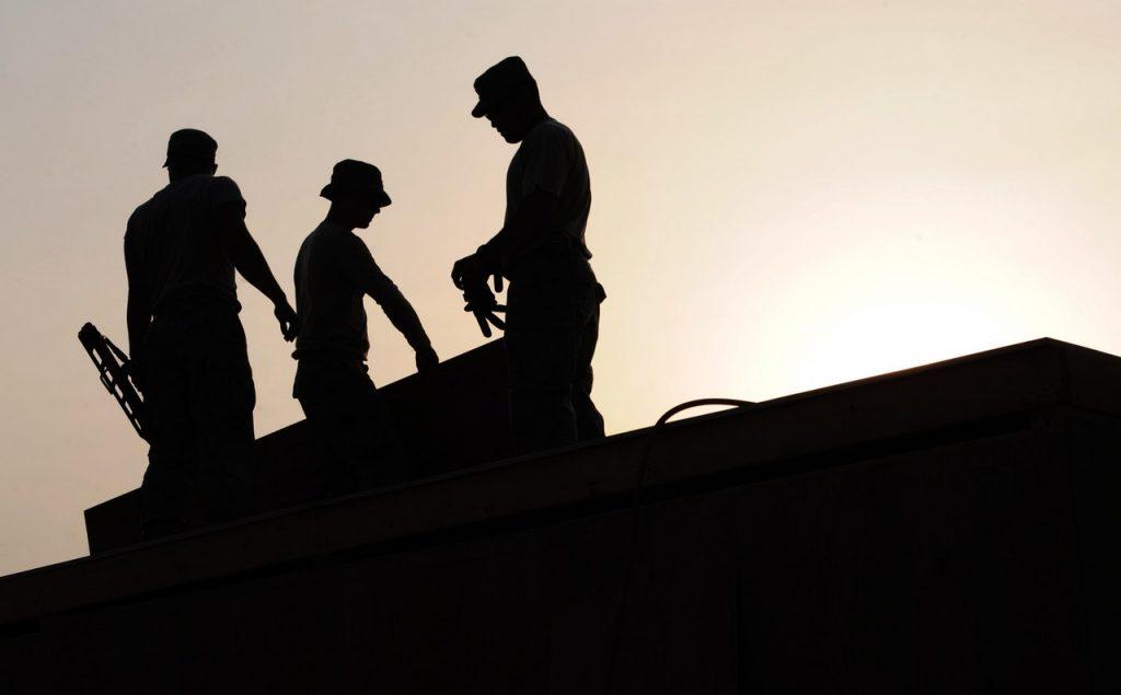 Hommes travaillants sur une toiture fin de journée