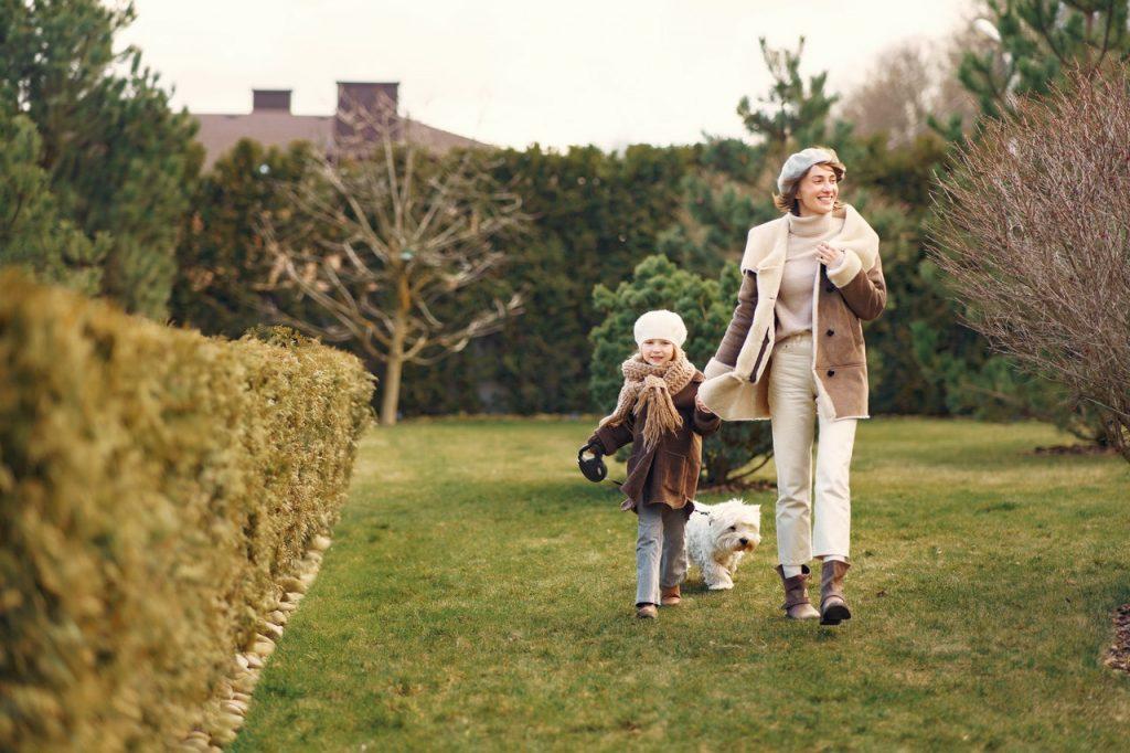 Mère et fille promenant leur petit chien à côté d'un buisson