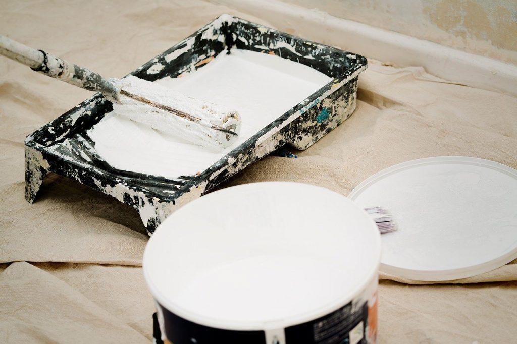 Pot de peinture blanche, rouleau et bac