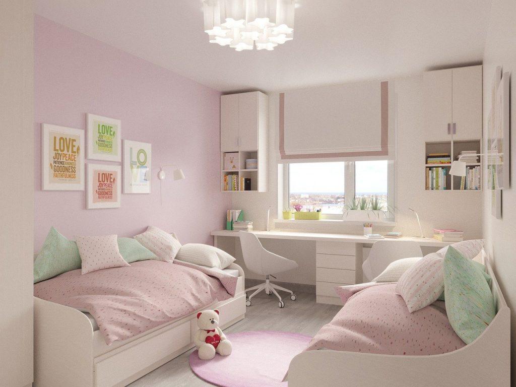 Chambre de fille rose avec deux lit et un long bureau, plusieurs rangements