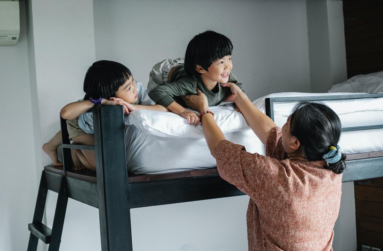 Deux enfants sur un lit superposé, lit à étage, adulte près d'eux