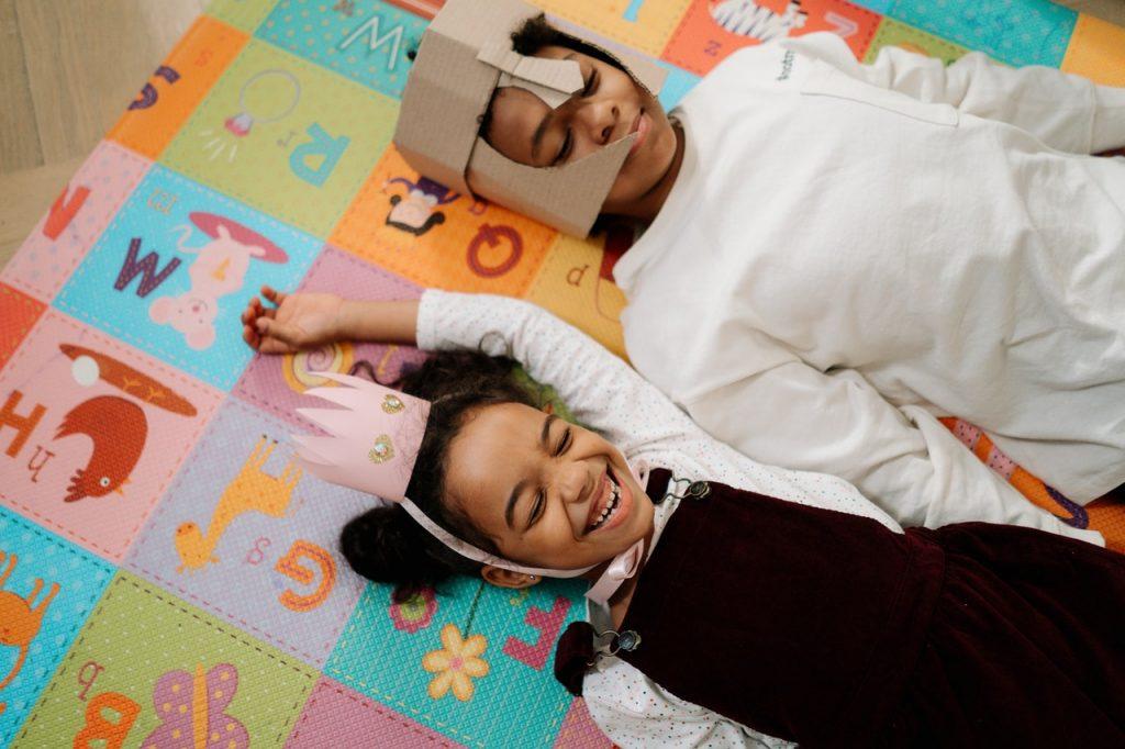 Deux enfants jouant au chevalier et la princesse, allongé sur un tapis
