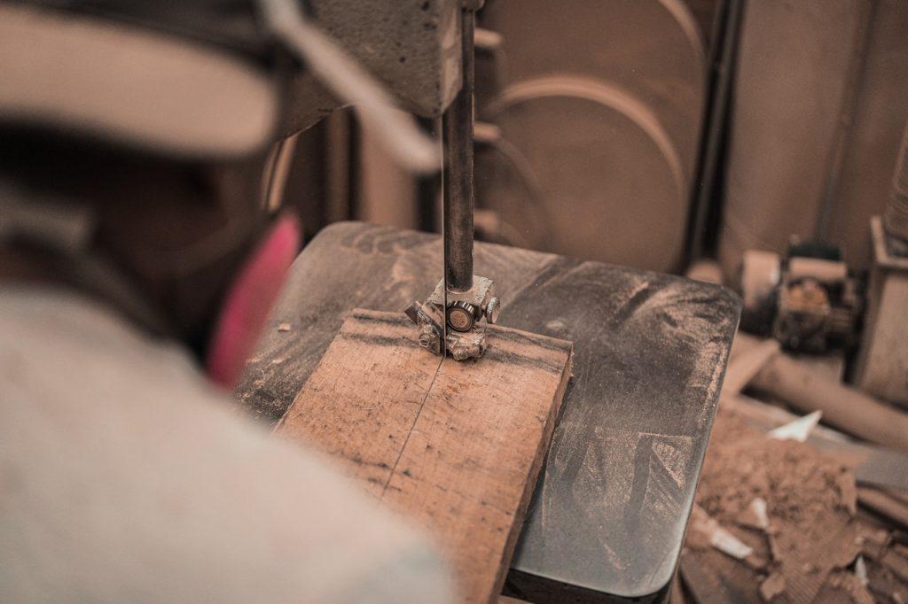 Homme découpant une planche avec une scie sur table