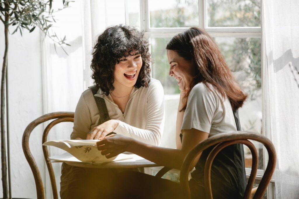 Deux femme assises et discutant ensemble, heureuses et souriantes