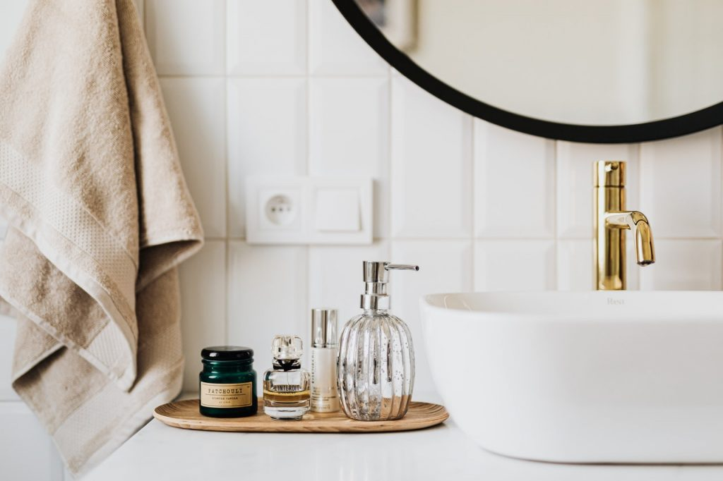 Carrelage blanc, lavabo, produit hygiène et miroir salle de bain