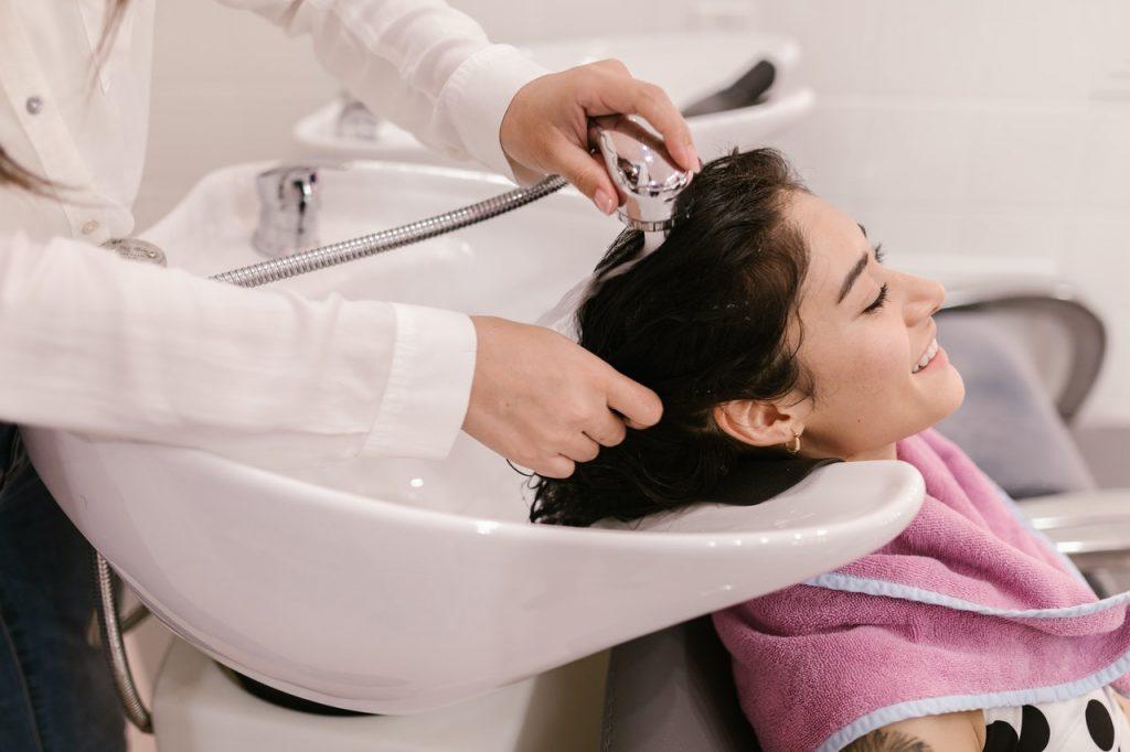 Femme dans un salon de coiffure faisant soin dans bac à shampoing