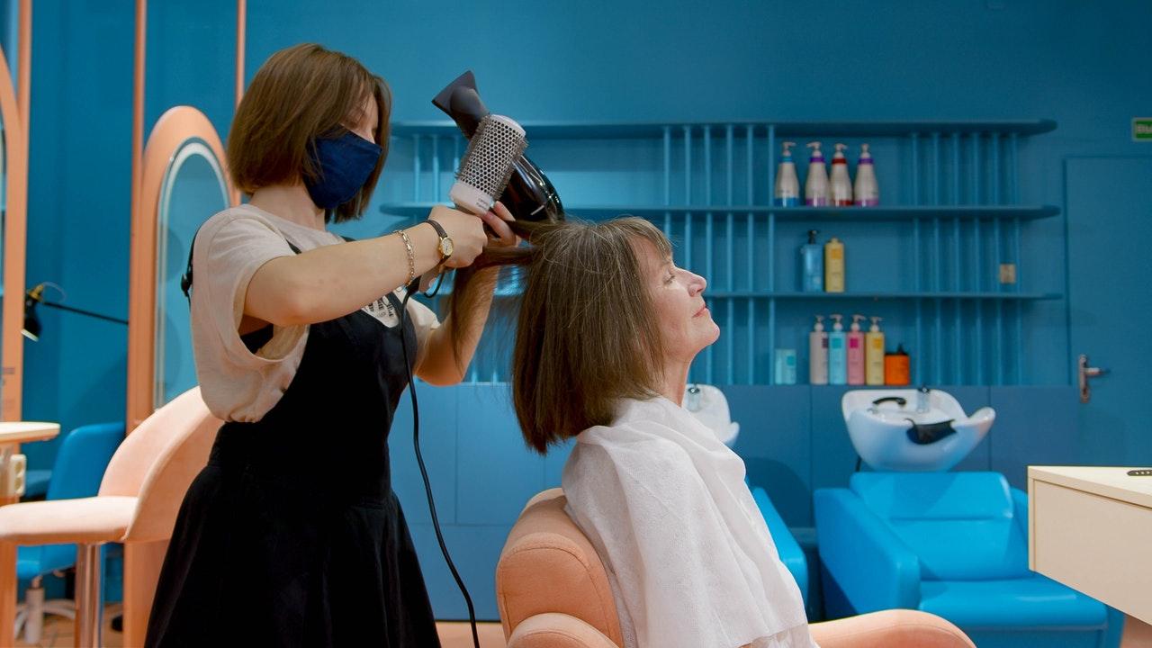 Coiffeuse séchant les cheveux d'une client dans son salon