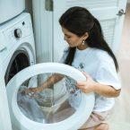 Femme faisant une machine à laver dans sa buanderie